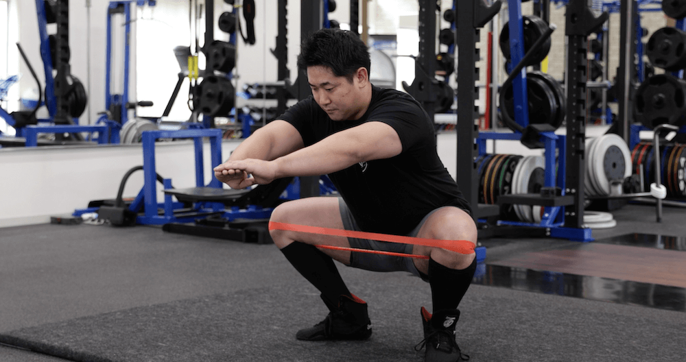 The Squat Ascent - practicing the knees out position using a resistance band.